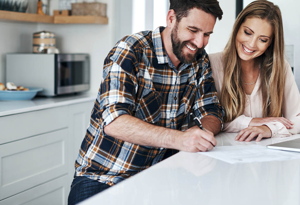 Young couple in kitchen signing home loan