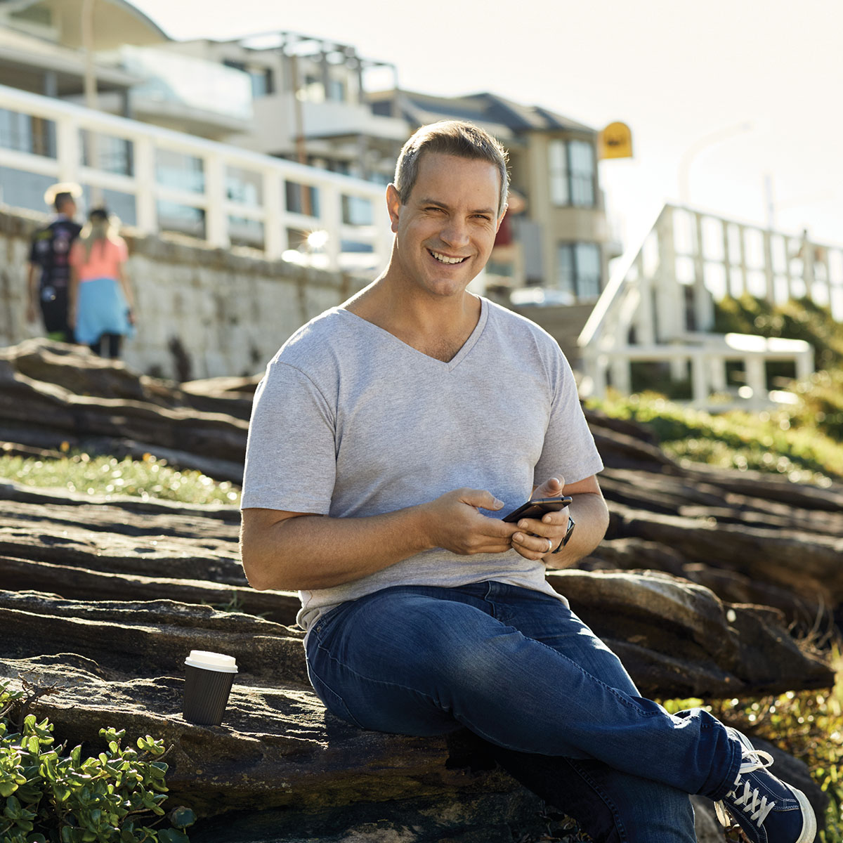 A man sitting with a legged crossed over and holding his phone. His sitting on rocks near a beachfront properties. Macquarie customer - Warren