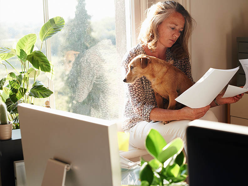 Woman with dog reviewing paperwork in sunny home office