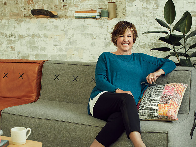 A middle aged woman dressed casually in a well decorated lounge room lounges on a couch smiling. Macquarie customer - Jane