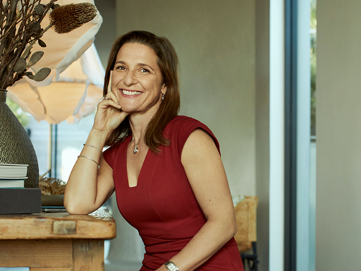 A woman dressed professionally in a red dress sitting in a modern furnished home, smiling at the camera. Macquarie - Kristen