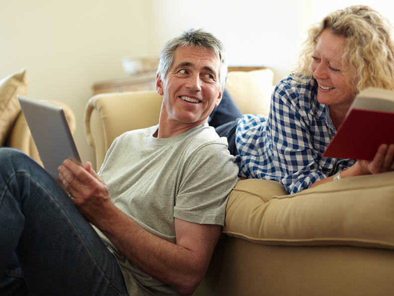 middle-aged couple on lounge smiling at each other